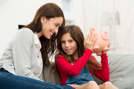 Smiling Mother Looking At Her Daughter Sitting On Couch Holding Piggybank