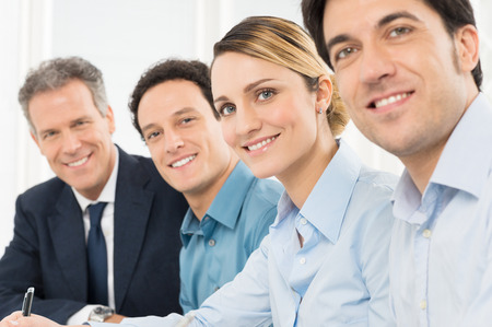 Foto de Portrait Of Smiling Businesspeople Looking At Camera Sitting In A Row - Imagen libre de derechos