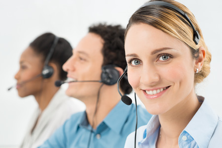 Foto de Smiling Woman With Headsets Working With Other Colleague In Call Center - Imagen libre de derechos