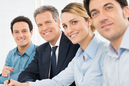 Portrait Of Happy Businesspeople Looking At Camera Sitting In A Row At Officeの写真素材
