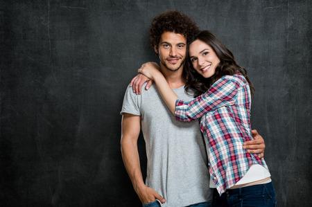 Photo pour Portrait Of Beautiful Young Couple Over Blackboard - image libre de droit