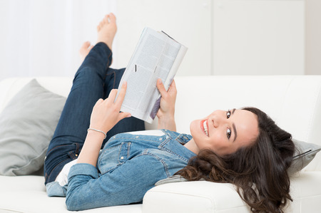 Smiling Happy Woman Lying On Sofa Reading A Magazine