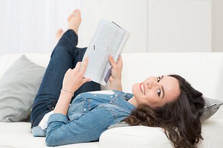 Foto de Smiling Happy Woman Lying On Sofa Reading A Magazine  - Imagen libre de derechos