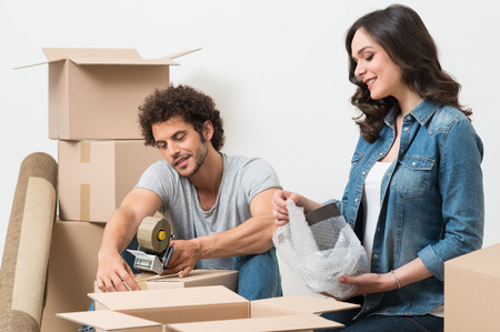 Portrait Of Happy Young Couple Packing Cardboard Boxes