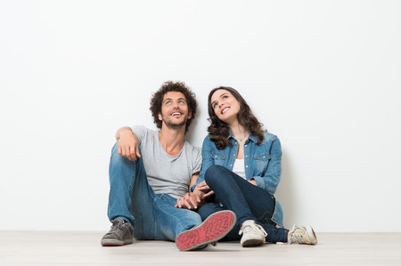 Portrait Of Happy Young Couple Sitting On Floor Looking Up Ready for your text or product