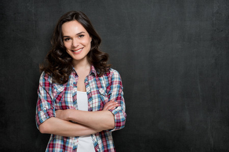 Happy Young Woman Smiling With Armcrossed Over Blackboard With Copy Space For Your Text