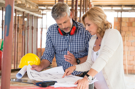 Portrait Of Male Architect And Mature Woman Discussing Plan On Blueprint At Construction Site
