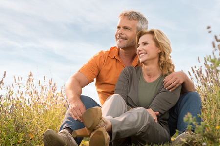 Portrait Of A Happy Mature Couple Sitting In Field And Contemplate The Future