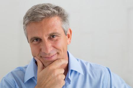 Photo pour Closeup Of Smiling Mature Man With Hand On Chin - image libre de droit