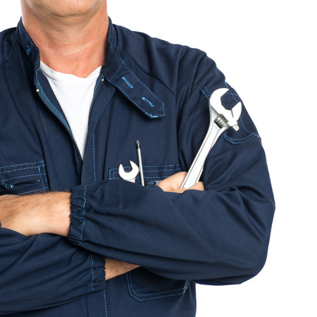 Closeup Of A Mechanic With Arm Crossed Holding Spanner Isolated On White Background