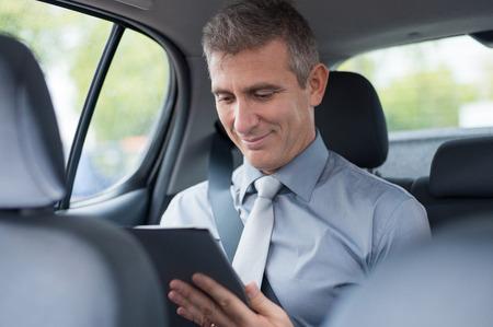 Closeup Of Mature Businessman In Car Working At Digital Tablet