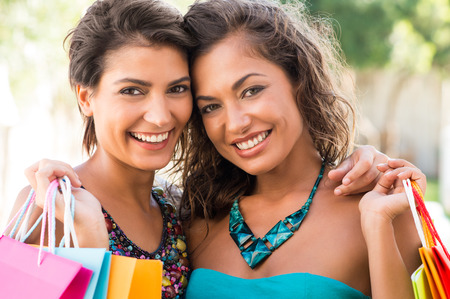 Portrait Of Two Beautiful Young Women Holding Shopping Bags Outdoor