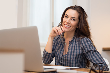 Beautiful casual businesswoman smiling and looking at camera in her office