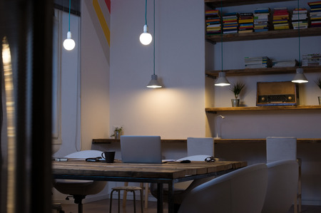 Photo for Laptop on desk with empty chairs in modern office - Royalty Free Image