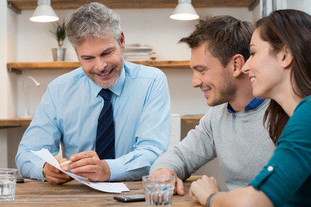 Photo pour Young couple consulting financial agent for new future projects - image libre de droit