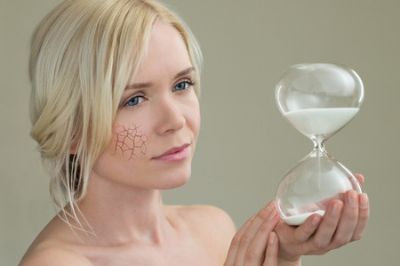 Beauty portrait of young woman holding hour glass sand timer, aging process concept