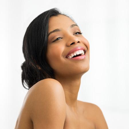 Foto de Closeup of happy young woman looking away isolated on white background - Imagen libre de derechos
