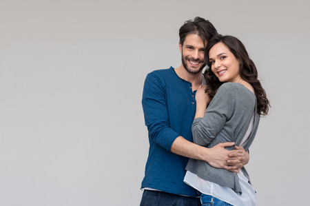 Foto de Portrait of happy couple looking at camera against gray background - Imagen libre de derechos