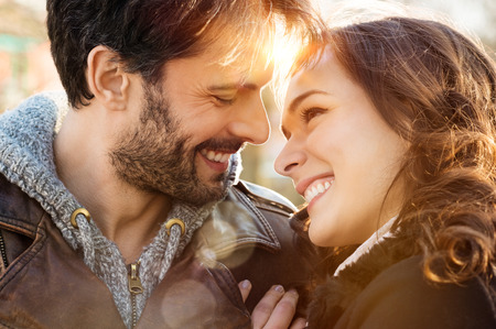 Photo pour Portrait of happy young couple looking at each other and smiling outdoor - image libre de droit