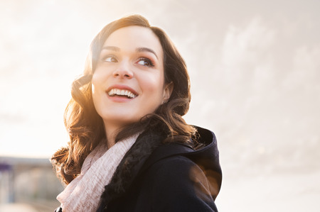 Closeup of smiling thinking woman looking away outdoor