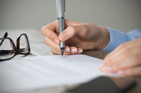 Photo pour Closeup shot of a woman signing a form. Businesswoman signing a new agreement at office. Shallow depth of field with focus on tip of the pen. - image libre de droit