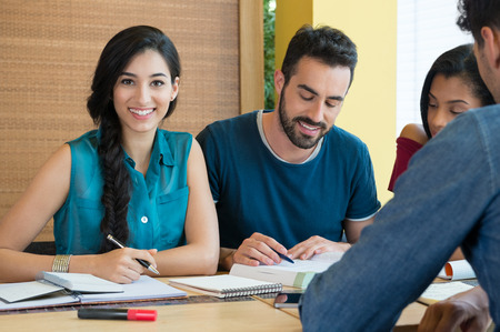Foto de Closeup of young woman looking at camera while studying with her friends at library. Portrait of female student preparing for the exam.Beautiful young woman looking at camera. - Imagen libre de derechos