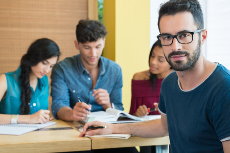 Foto de Closeup shot of young man looking at camera. Male student preparing university exam. Shallow depth of field with focus on handsome young man making note. Portrait of guy with eyeglasess with others students studying in background. - Imagen libre de derechos