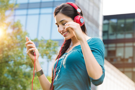 Closeup shot of young woman listening to music with mobile phone outdoor. Happy smiling girl listening to music with earphone. Portrait of carefree woman listening to music in a city center.