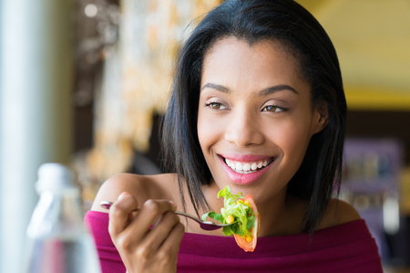 Closeup shot of young woman eating fresh salad at restaurant. Healthy african girl eating salad and looking away. Smiling young woman holding a forkful of salad. Health and diet concept. Woman ina a lunch break.