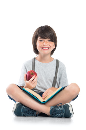 Closeup of smiling little boy studying isolated on white background. Portrait of laughing schoolboy sitting on floor and doing homework. Happy young boy eating a red apple and looking at camera with funny face.