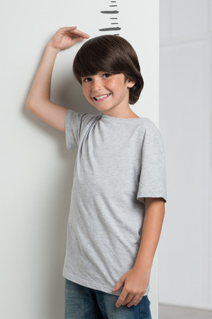 Closeup of little boy measuring height himself against white wall. Boy growing tall. Smiling cute boy measures his height with his hand on the head. Happy growing boy looking at camera.