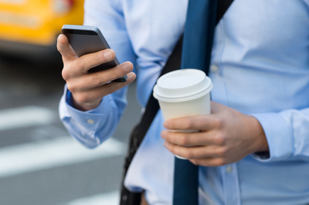 Foto de Close up of a businessman using mobile phone and holding paper cup. Close-up detail of a businessman's hand holding paper cup and using a smartphone while walking on the road. Man going at work. - Imagen libre de derechos