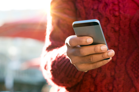 Photo for Close up of a young woman's hand typing text message on her smartphone. African young woman is typing on touch screen mobile phone. Close up of female hand texting a message phone outdoor. - Royalty Free Image
