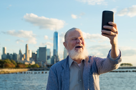 Photo for Happy smiling senior man taking a selfie in a beautiful day at river side. Senior healthy man enjoying is retirement. Casual joyful grandfather taking a selfie with the skyscrapers in the background at sunset. - Royalty Free Image