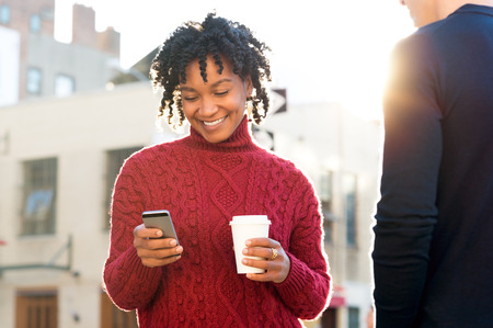 Photo for Young woman standing with friend texting on the phone and holding a take away paper up of coffee. African girl with paper cup writing text message with smart phone while walking on road. African woman with cellphone and coffee smiling. - Royalty Free Image