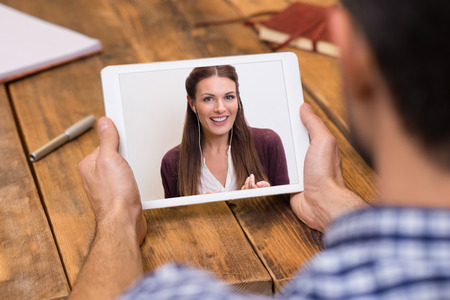 Photo for Closeup of a woman talking through video chat on tablet. Young man communicating with his girlfriend on tablet in video chat. Young man looking at screen of tablet and talking with a woman trought webcam. - Royalty Free Image