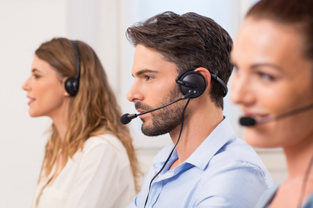 Foto de Happy young employees working in call centre. Portrait of a young attractive telephone operator working in a call center. Customer service representative wearing a headset at the office. - Imagen libre de derechos