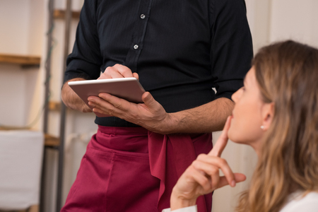 Photo pour Close up of waiter's hand noting down menu on tablet. Young woman ordering for food to a waiter at restaurant. Young beautiful woman thinking of food to order in front of a waiter holding tablet. - image libre de droit