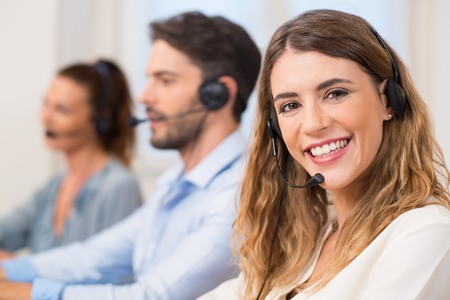 Foto de Smiling female call centre operator doing her job with a headset while looking at the camera. Portrait of happy woman in a call center smiling and working. Portrait of happy smiling female customer support phone operator at workplace. - Imagen libre de derechos