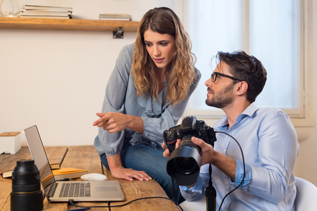 Photo pour Young photographers looking at photographs on laptop. Assistant photographer helping photographer in the selection of photos. Young team of photographer working in a professional studio. - image libre de droit