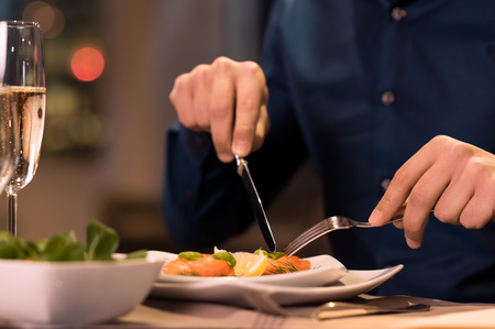 Photo pour Close up of a male hands cutting and eating delicious salad with knife and fork at restaurant - image libre de droit