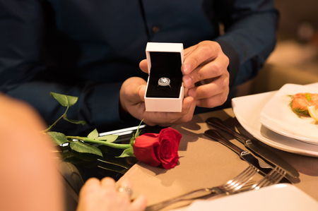 Photo for Young man presenting engagement ring to girlfriend. - Royalty Free Image