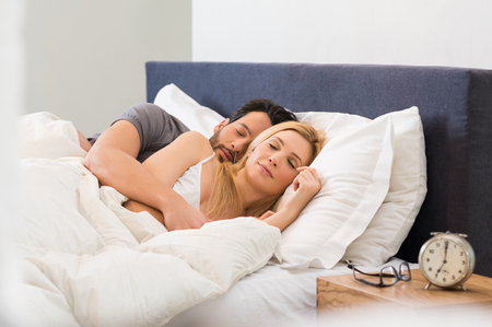 Photo pour Young adult couple sleeping peacefully on the bed in bedroom. - image libre de droit