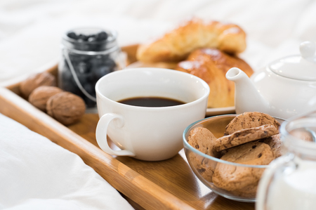 Close up of a cup of tea with cookies on wooden tray in bed.
