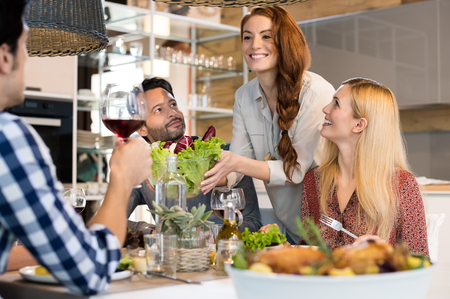 Smiling woman serving salads to her friends at home.