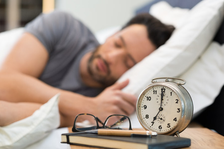 Photo pour Man sleeping with an alarm clock in foreground. - image libre de droit