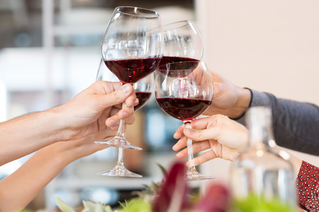Photo pour Closeup of friends toasting glasses of red wine in a party. - image libre de droit