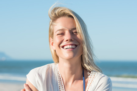 Photo pour Portrait of a young cheerful woman smiling at the beach. Young blonde enjoying on a bright sunny day at the beach. Portrait of happy girl laughing and looking at camera. - image libre de droit