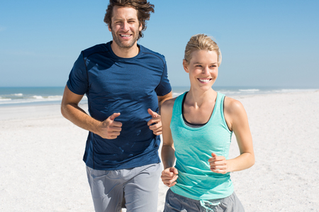 Foto de Couple exercising at beach. Trainer training athlete for fitness. Athletics jogging in summer sport shorts enjoying the sun. - Imagen libre de derechos