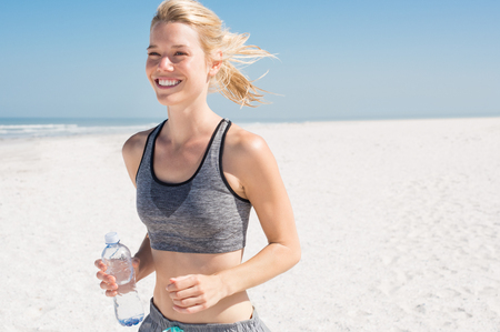 Young woman jogging on the beach in summer day. Athlete runner exercising actively in sunny morning. Blonde girl preparing herself for marathon.